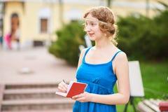 Piękny artysta na ulicie w błękitnym smokingowym writing coś w notatniku Zdjęcie Royalty Free