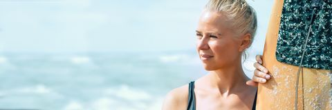 Piękny atlety dziewczyny surfingowiec z deską przy wschód słońca Wakacje przy morzem, zdrowy styl życia sztandar zdjęcie stock