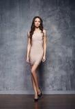 Piękny, atrakcyjny model pozuje w beżowej sukni, Obraz Stock