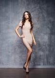 Piękny, atrakcyjny model pozuje w beżowej sukni, Obrazy Royalty Free
