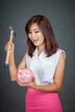 Piękny Azjatycki dziewczyny liźnięcie jej wargi wokoło uderzać pieniądze pudełko z h Fotografia Royalty Free