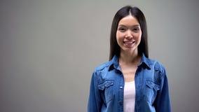 Piękny azjatykci żeński ono uśmiecha się, stojący przeciw popielatemu tłu, miejsce dla teksta obrazy royalty free