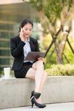 Piękny azjatykci biznesowej kobiety mądrze telefon i cyfrowa pastylka Obrazy Royalty Free