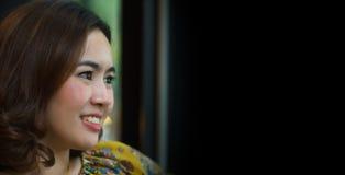 Piękny azjatykci kobieta uśmiech i widzii coś z czarnym tłem i kopiuje przestrzeń dla teksta Obraz Royalty Free