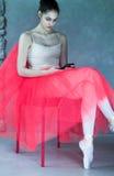 Piękny baletniczego tancerza obsiadanie wewnątrz relaksuje z telefonem Obraz Stock