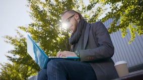 Piękny biznesmen outdoors siedzi na ławce wewnątrz w szkłach ubierał w kurtce z szalikiem używać laptop na przerwie zbiory wideo
