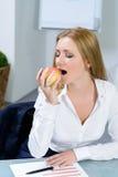 Piękny bizneswoman je jabłka w biurze Obrazy Royalty Free