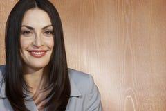 Piękny bizneswoman ono Uśmiecha się Przeciw Drewnianej ścianie Obraz Royalty Free