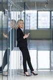 Piękny bizneswoman używa smartphone w biurze Zdjęcia Royalty Free