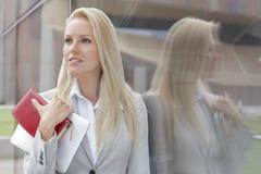 Piękny bizneswomanu mienia organizator i cyfrowa pastylka podczas gdy patrzejący daleko od szklaną ścianą zdjęcie stock