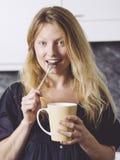 Piękny blond mieć kawę w jej kuchni obraz royalty free