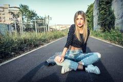 Piękny blondynki dziewczyny obsiadanie na ulicie w miasteczku zdjęcie royalty free