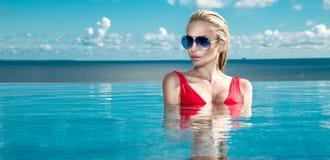Piękny blondynki kobiety model z mokrym włosy i elegancki makeup obsiadanie w basenie Fotografia Stock