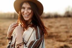 Piękny boho kobiety modniś, ono uśmiecha się, będący ubranym kapelusz i poncho przy zmierzchem w górach, prawdziwe emocje, przest zdjęcia royalty free