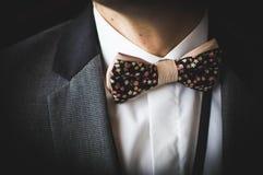 Piękny brązu łęku krawat z małymi kolorowymi kwiatami na białej koszula i popielatej kurtce zdjęcia royalty free