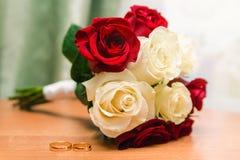 Piękny bridal bukiet róże i złociste obrączki ślubne białe i czerwone zdjęcia royalty free