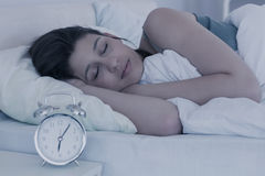 Piękny brunetki dosypianie w jej łóżku Zdjęcia Royalty Free