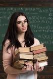 Piękny brunetki dziewczyny mienia rozsypisko książki w jej rękach Mądrze studencki narządzanie dla egzaminów zdjęcie stock