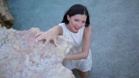 Piękny brunetki dziewczyny odprowadzenie na stromej kamień plaży zbiory