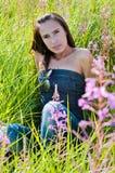 Piękny brunetki kobiety obsiadanie w polu fotografia stock