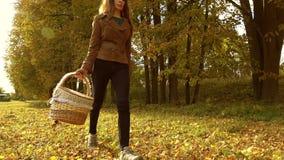 Piękny brunetki kobiety odprowadzenie przez jesieni drewien, mienie pykniczny kosz słoneczny dzień Zwolnionego tempa steadicam wi zbiory
