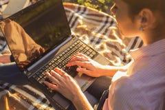 Piękny brunetki kobiety studiowania obsiadanie na szkockiej kracie pisać na maszynie na a Zdjęcie Royalty Free