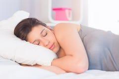 Piękny brunetki lying on the beach na łóżkowym dosypianiu Obrazy Stock