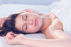 Piękny brunetki lying on the beach na łóżkowym dosypianiu Zdjęcie Stock