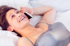Piękny brunetki lying on the beach na łóżku opowiada na telefonie Obraz Royalty Free