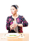 Piękny brunetki młodej kobiety czas oczekiwania jeść ogórek na białym tle Obrazy Royalty Free