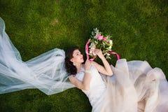Piękny brunetki panny młodej lying on the beach w trawie zdjęcia stock