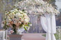 Piękny bukiet róże w wazie na tle ślubu łuk Piękny ustawianie dla ślubnej ceremonii Zdjęcia Royalty Free