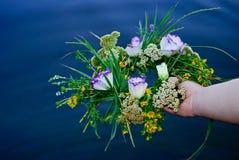 Piękny bukiet wianek wildflowers dziewczyna trzyma rzekę nad wodą zdjęcie royalty free