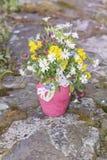 Piękny bukiet z dzikimi kwiatami w różowej wazie z faborkiem Obrazy Royalty Free