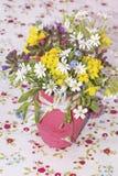 Piękny bukiet z dzikimi kwiatami w różowej wazie z faborkiem Obrazy Stock