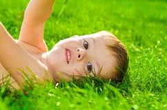 Piękny chłopiec lying on the beach na trawie obraz royalty free