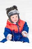 Piękny chłopiec obsiadanie na śniegu zdjęcia royalty free