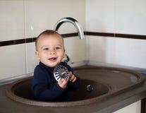 Piękny chłopiec obsiadanie w zlew Fotografia Stock