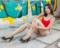 Piękny Chiński kobiety obsiadanie graffiti ścianami Fotografia Stock