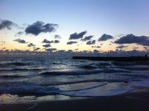 piękny chmurny świt kołysa niebo denną wodę Zdjęcie Stock