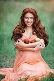 Piękny ciążowy pojęcie Brunetki kobiety szczęśliwy obsiadanie na trawie z kędzierzawym włosy na natury tle Fotografia Stock