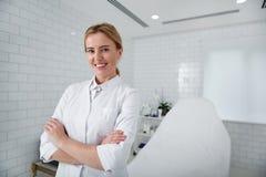 Piękny cosmetologist stoi w jej gabinecie z krzyżować rękami zdjęcia royalty free