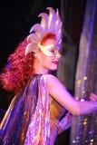Piękny czerwony dziewczyna magika ` s asystent Mistrza magika iluzjonista pokazuje na wewnętrznego projekta scenie Fotografia Stock