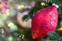 Piękny czerwony ornament na choince z iskrzastymi światłami białymi i miękkim tłem zdjęcie royalty free