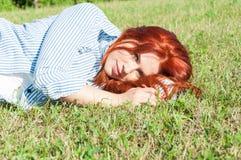 Piękny czerwony z włosami kobiety lying on the beach na traw outdoos Zdjęcia Stock