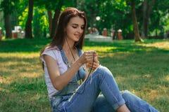 Piękny damy obsiadanie w parku na słonecznym dniu i słucha muzyka Zdjęcia Royalty Free