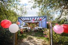 Piękny dekorujący drewniany pawilon z baloons i bukiet róż pastelowych kolorów stołu pozycja na zielonej trawie blisko drzewo pog Zdjęcia Royalty Free