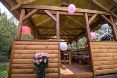Piękny dekorujący drewniany pawilon z baloons i bukiet róż pastelowych kolorów stołu pozycja na zielonej trawie blisko drzewo pog Fotografia Stock