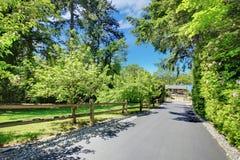 Piękny dom z intymnymi bramami, długim podjazdem i ogródem. Zdjęcie Stock