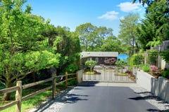 Piękny dom z intymnymi bramami, podjazdem i ogródem. Zdjęcia Stock